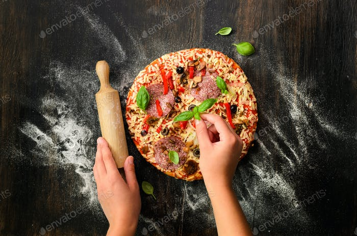 Girl hands making, decopating, preparing pizza with basil leaves on dark background. Top view, copy
