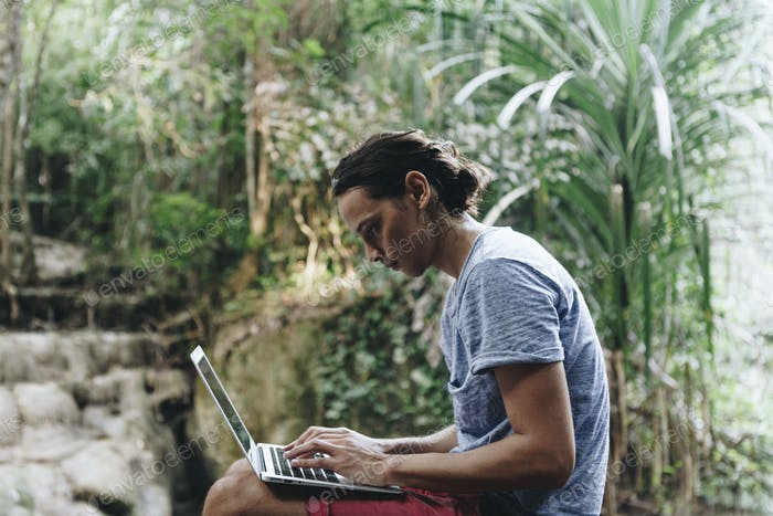 White man using computer laptop at waterfall