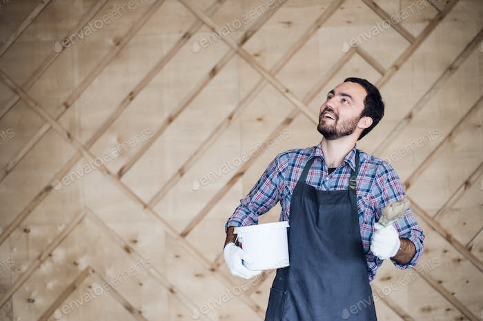 Man with tin of paint and brush looking up on a wooden wall background. Copy space for your text