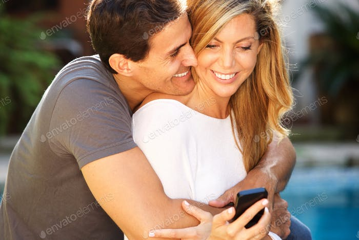 Close up smiling couple sitting outside in embrace looking at smart phone