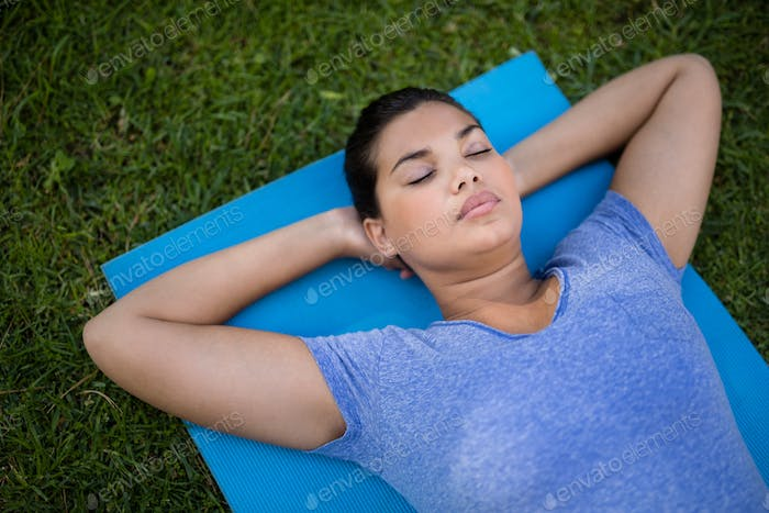 Young trainer relaxing on exercise mat