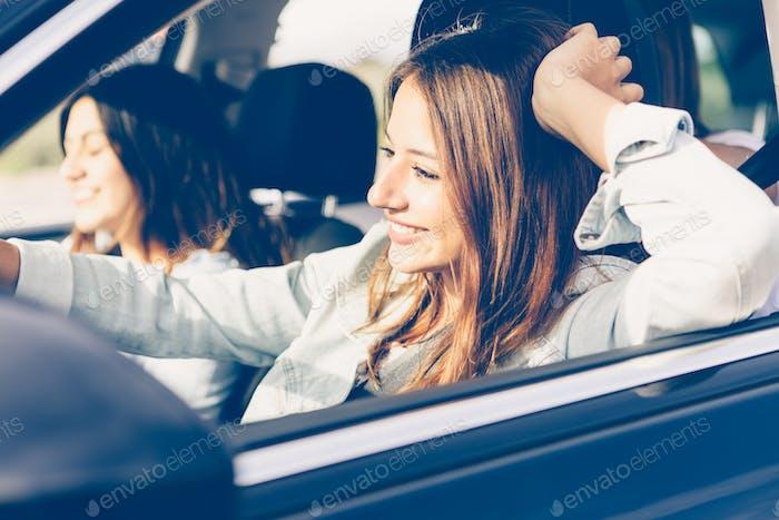 Glückliche Mädchen fahren ein Auto