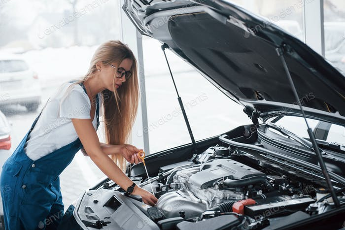 On the lovely job. Car addicted woman repairs black automobile indoors