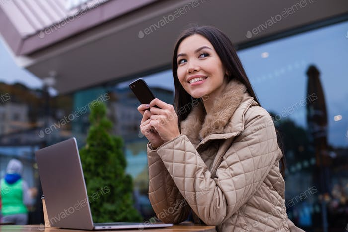 Young attractive woman in down jacket slyly looking away using cellphone in cafe on street