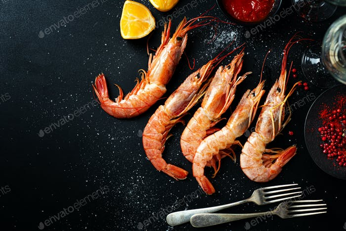Uncooked giant shrimps on dark table