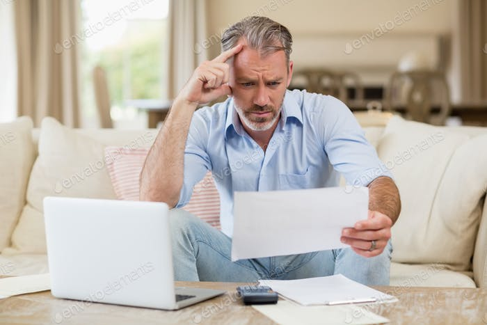 Tense man looking at bills in living room