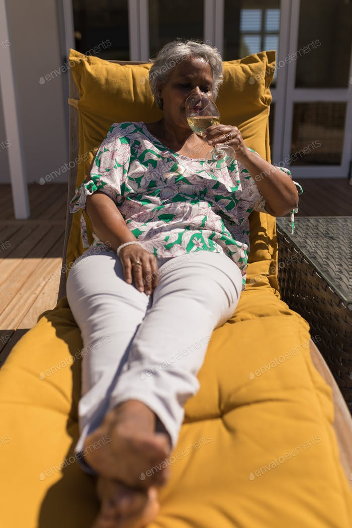 Senior woman drinking champagne while relaxing on a lounger chair in the backyard of home