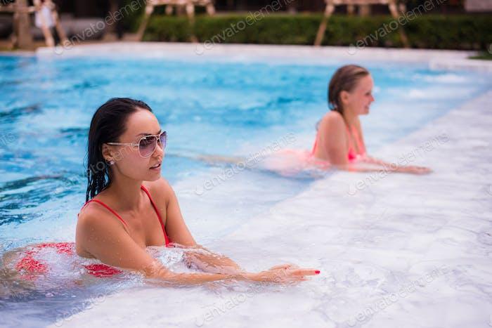 two young beautiful women in jacuzzi of resort