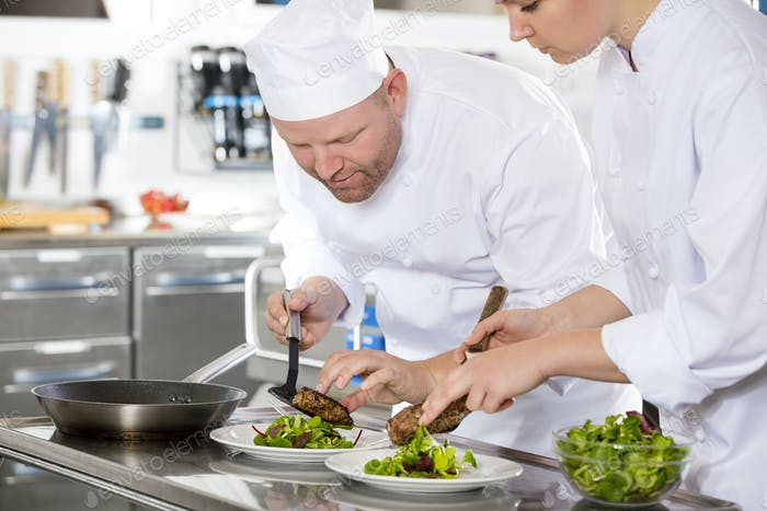 Smiling professional chef prepare steak dish at restaurant