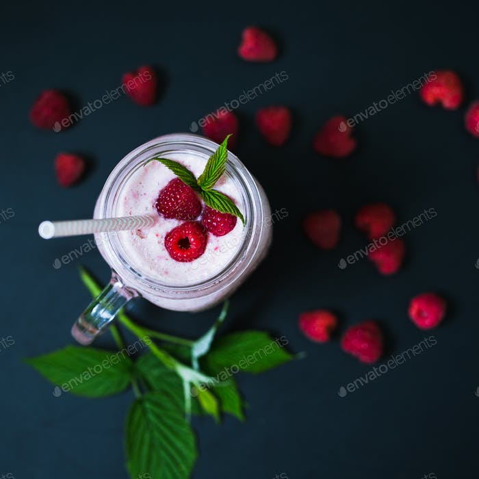 Pink raspberry smoothie in a mason jar with straws on a black background