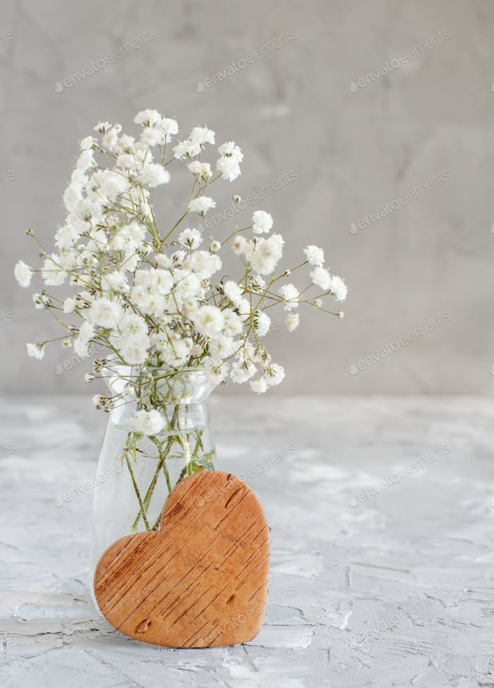 Bouquet of small white flowers and wooden hearts