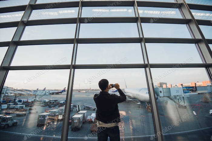 traveler with mobile phone at the airport taking picture of his aircraft. Air Traffic Control