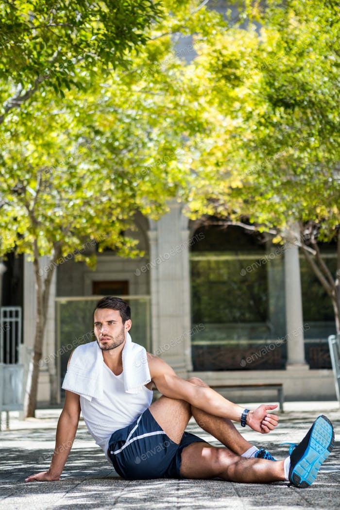 Handsome athlete with towel stretching his leg on the ground in the city