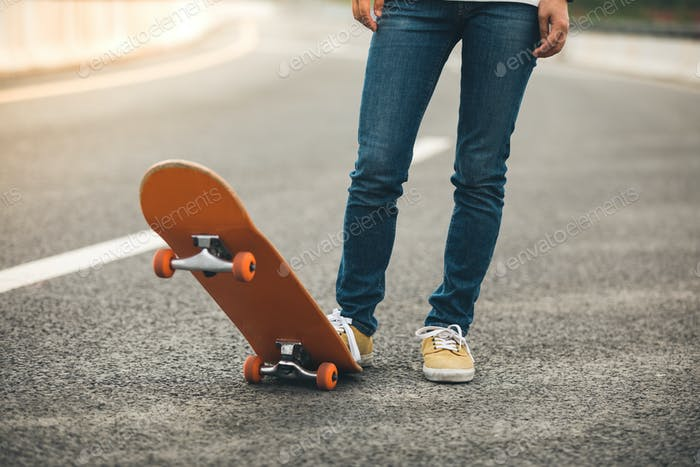 Skateboarder with skateboard on highway ready for riding