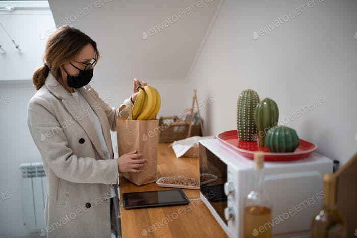 Woman in mask taking purchases from bag at home