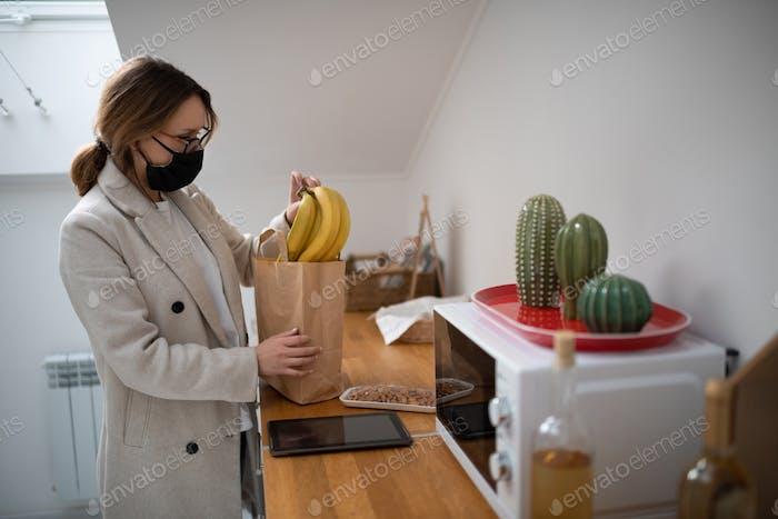 Frau in Maske, die Einkäufe aus Tasche zu Hause