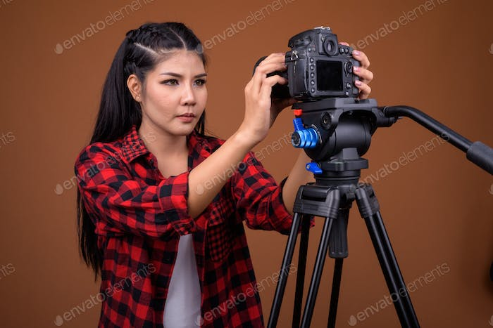 Young Asian woman photographer adjusting camera on tripod
