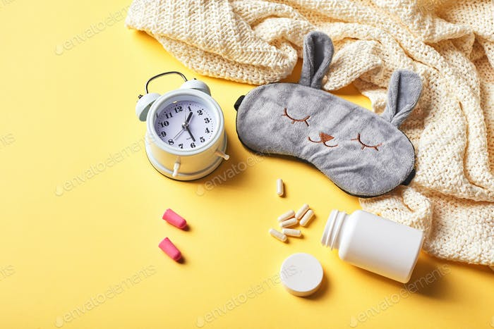 Sleeping mask, alarm clock, earplugs and pills on yellow. Healthy night sleep creative concept.