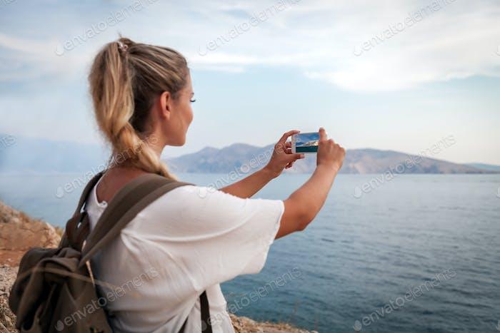 Wanderer Mädchen mit Smartphone macht Landschaftsfoto von Meeresbucht während der Reise