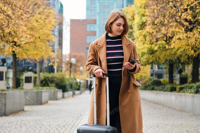 Attractive casual girl looking way on cellphone standing with suitcase on street