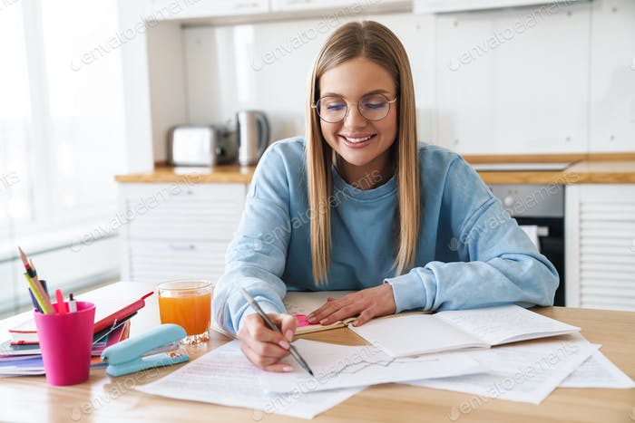 Image of pleased woman smiling while studying with exercise books