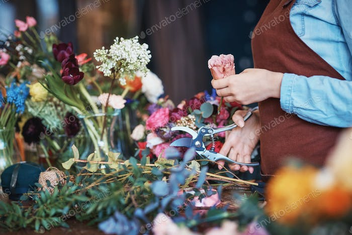 Young florist in uniform with flowers