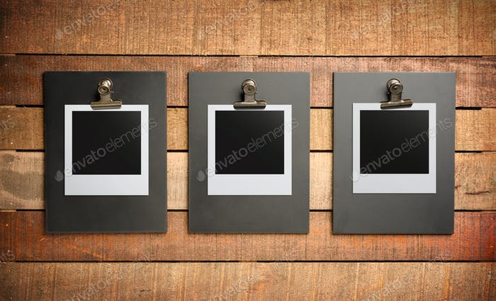 Three blank photos on wooden background
