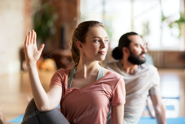 woman with group of people doing yoga at studio