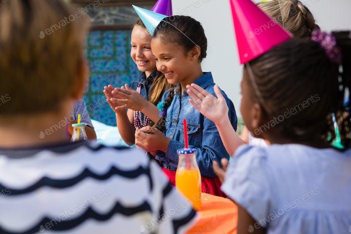Kinder applaudieren beim Sitzen am Tisch