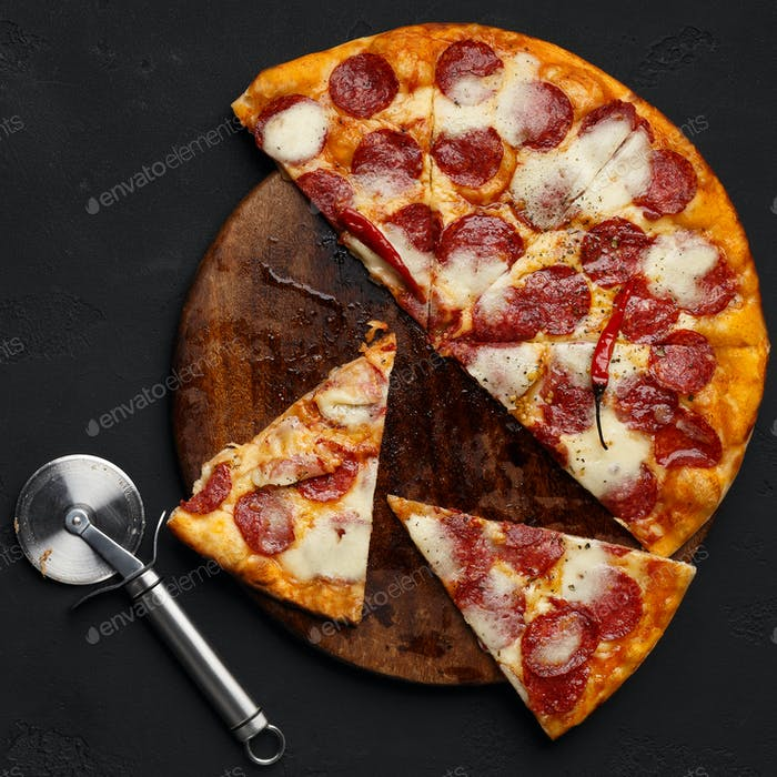 Cutted pepperoni pizza on cutting board with cutter nearby