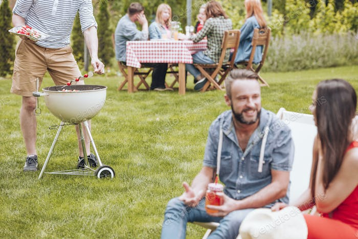 Man grilling shashliks during party