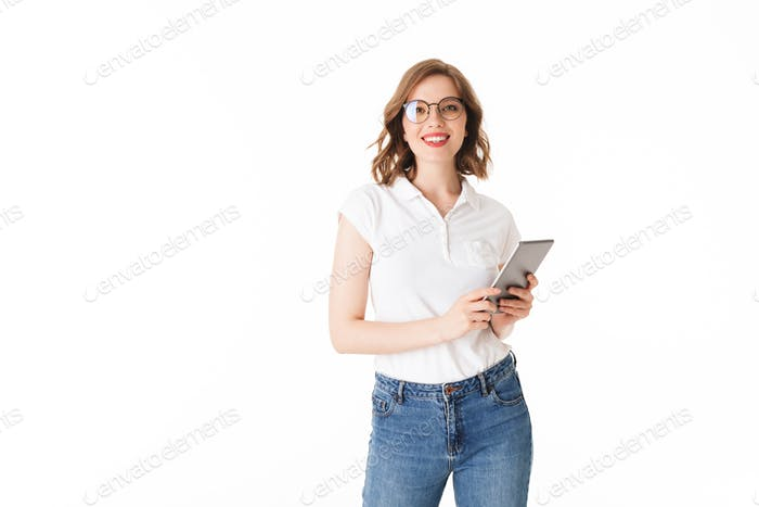 Beautiful lady in eyeglasses standing with the tablet in hands and happily looking in camera