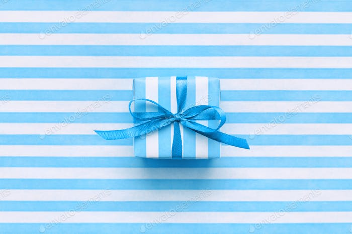 A Gift Box on Blue and White Striped Wrapping Paper.