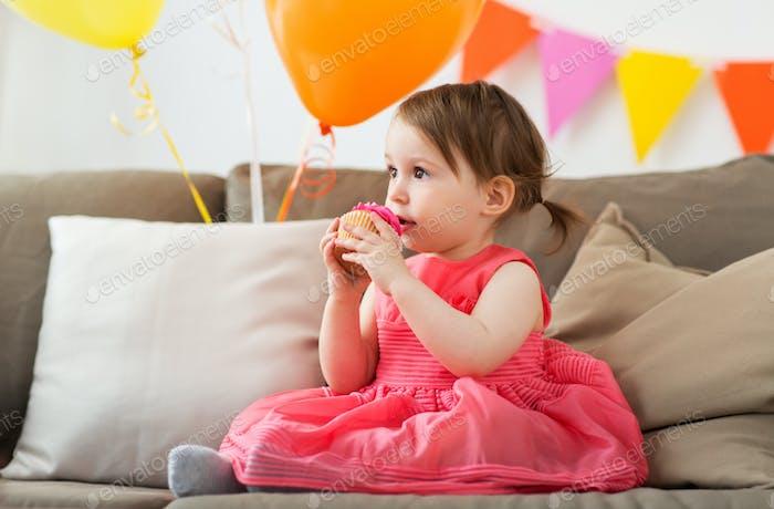 bebê feliz comendo cupcake na festa de aniversário