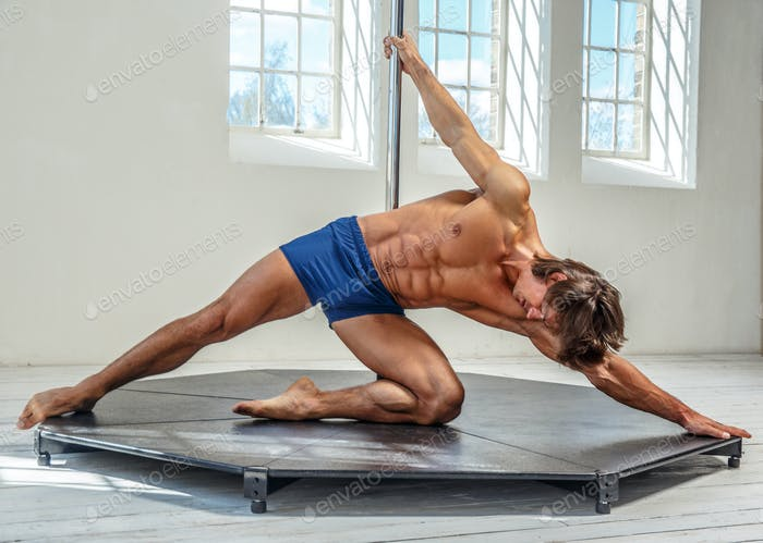 Man pole dancing in a hall with big windows.