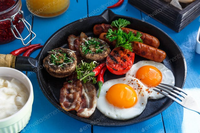 Englisches Frühstück in einer Pfanne mit Spiegeleier, Würstchen, Speck, Pilzen, Marmelade und Orangensaft
