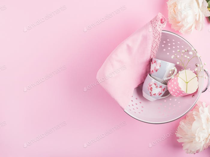 Pink colander with pink cups. Flat lay