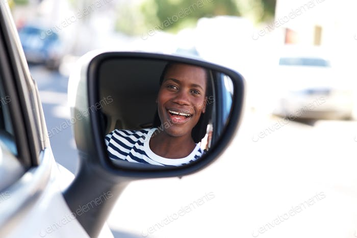 Close up happy african woman driving car and looking in side mirror