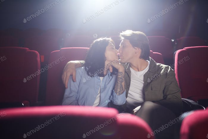 Young Couple Kissing in Cinema