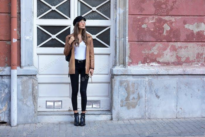 Mujer joven bonita mirando hacia los lados mientras está de pie en la calle.