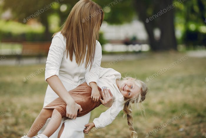 Mother with little daughter playing in a summer park