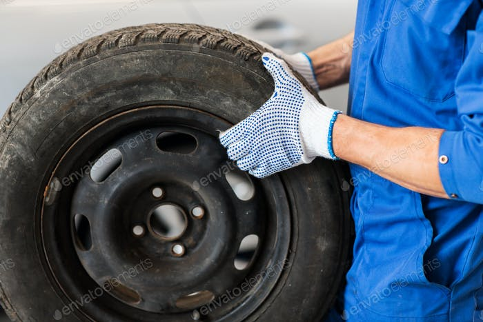 mechanic with wheel tire at car workshop