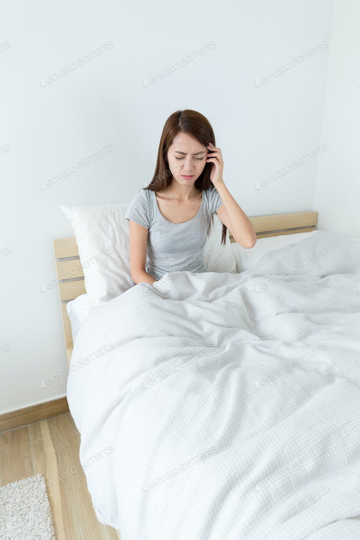 Young woman feeling unwell on bed
