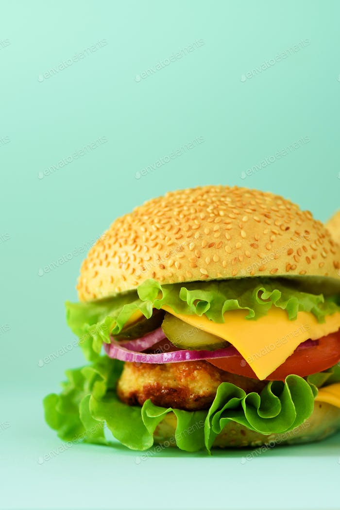 Macro view of tasty burger with beef, cheese, lettuce, onion, tomatoes on blue background. Close up