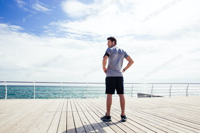 Sports man standing near sea outdoors