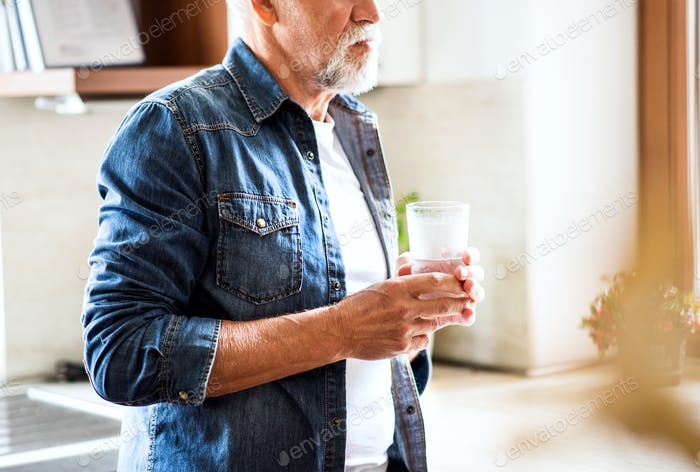 Senior man holding a glass of water in the kitchen.