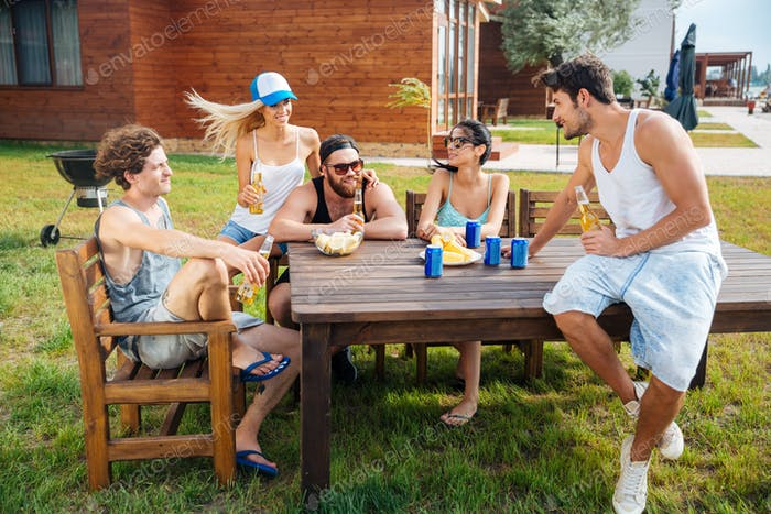 Group of happy young people sitting and drinking beer outdoors