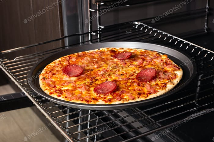 Cooking homemade pizza in an electric oven.