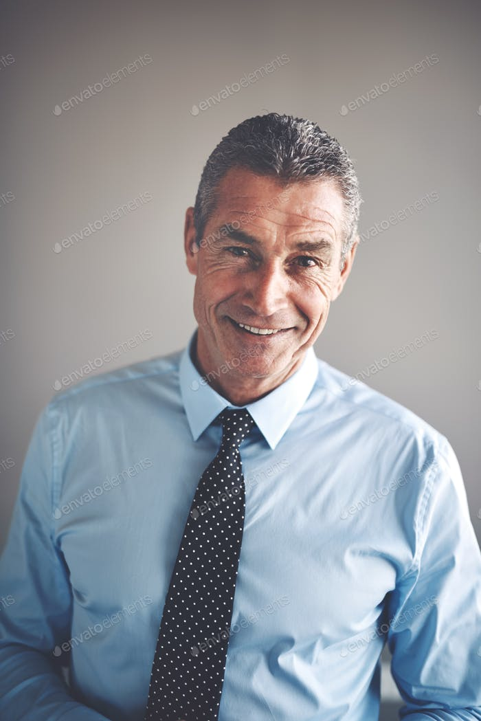 Smiling mature corporate executive wearing a shirt and tie