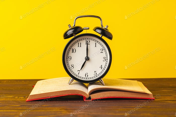 Books and alarm clock on table, education concept